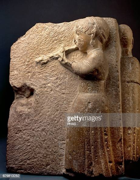 Iberian frieze relief depicting a woman or auletris dressed with tunic tied at the waist playing a flute named aulos In the hair double braid around...