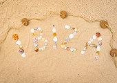 Word Ibiza writing with seashells on sandy beach