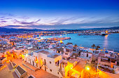 Elevated view over Ibiza Old Town and Harbour with ferries at dusk.