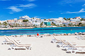Sunbeds and beautiful city view on a beautiful beach in Ibiza, Spain.