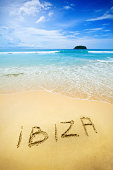 """""""Ibiza written on the sand of a beautiful tropical beach. Visible are one island in the sea, turquoise water, little splashy waves, golden sand and beautiful cloudscape over the sea.See more images li"""