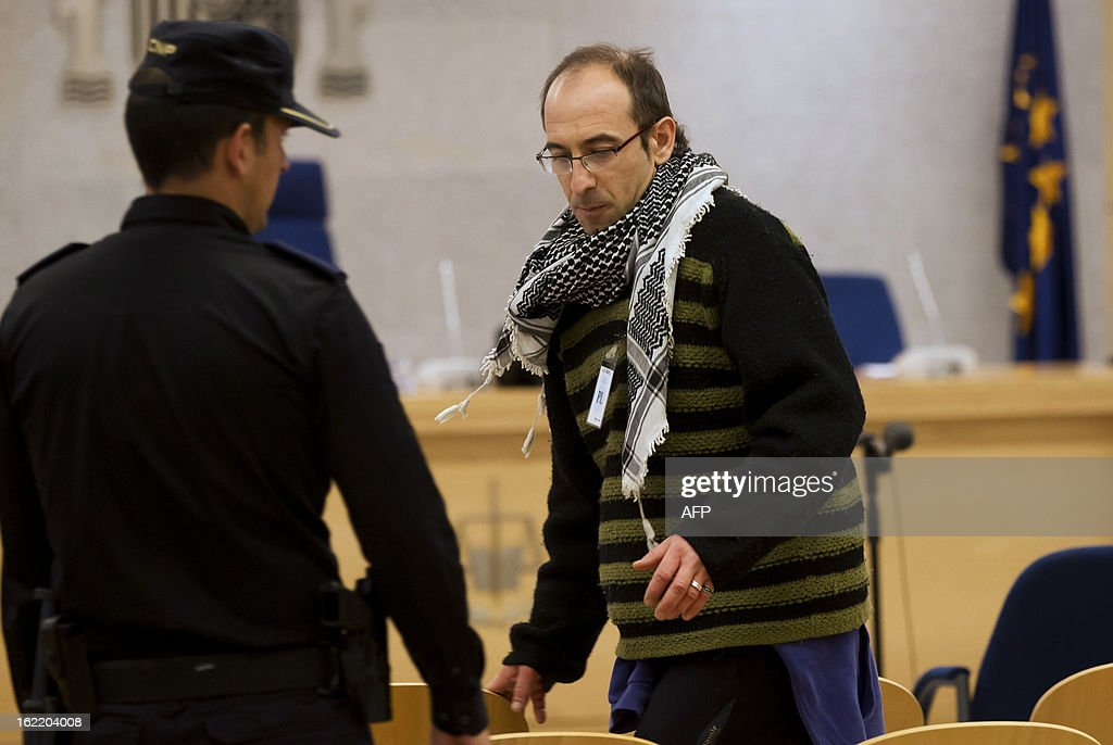 Ibon Iparraguirre (R), suspected member of the Basque armed separatist group ETA, arrives in the courtroom to attend his trial at the National Court in Madrid on February 18, 2013. Ibon Iparraguirre is charged with allegedly taking part in 2008 in a car bomb attack against an Ertzaintza station, Basque police station, in Ondarroa, injuring three police officers and five civilians. AFP PHOTO / POOL / CHEMA MOYA