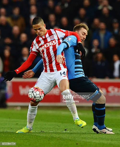 Ibrahim Afellay of Stoke City tussles with Christian Eriksen of Tottenham Hotspur during the Barclays Premier League match between Stoke City and...