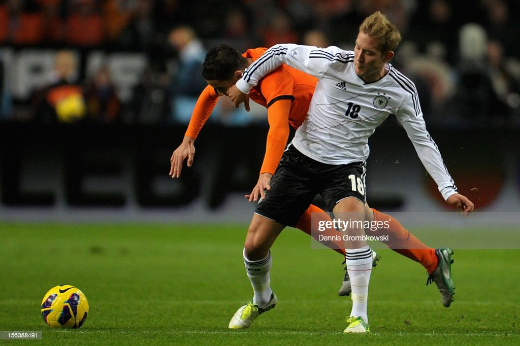 Ibrahim Affelay of Netherlands and <a gi-track='captionPersonalityLinkClicked' href=/galleries/search?phrase=Lewis+Holtby&family=editorial&specificpeople=5351202 ng-click='$event.stopPropagation()'>Lewis Holtby</a> of Germany battle for the ball during the International Friendly match between Netherlands and Germany at Amsterdam Arena on November 14, 2012 in Amsterdam, Netherlands.