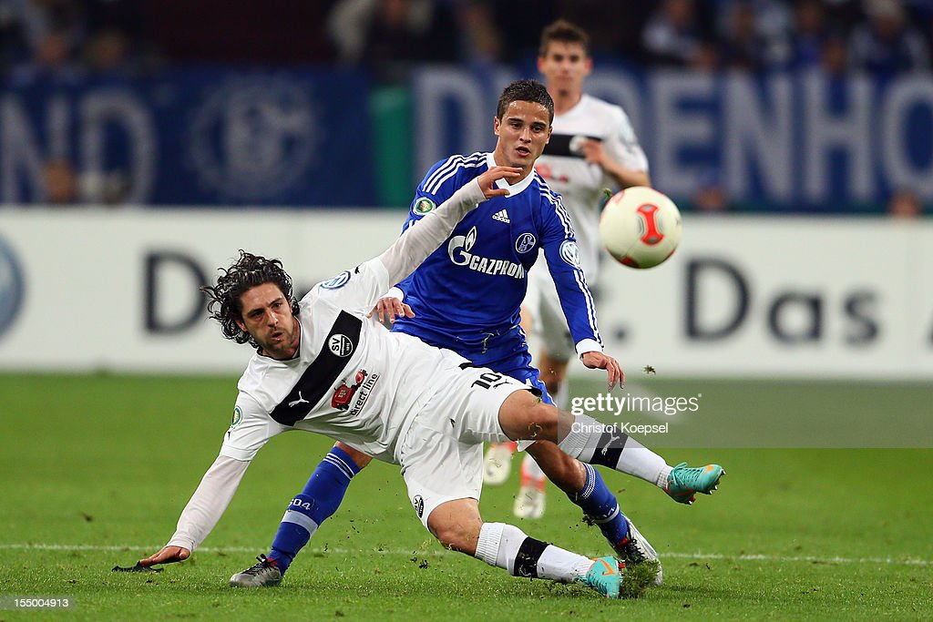 Ibrahim Affelay of Schalke (R) challenges David Ulm of Sandhausen (L) during the DFB Cup second round match between FC Schalke 04 and SV Sandhausen at Veltins-Arena on October 30, 2012 in Gelsenkirchen, Germany.