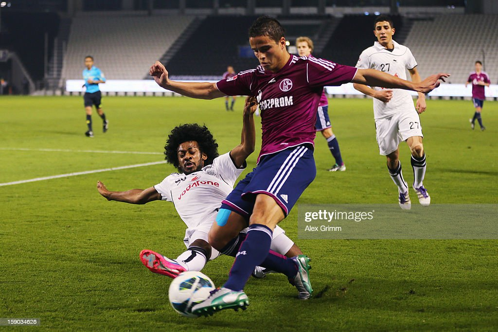 Ibrahim Affelay (R) of Schalke is challenged by Hamad Faraj Almass of Al Sadd during the friendly match between Al-Sadd Sports Club and FC Schalke 04 at Jassim Bin Hamad Stadium on January 6, 2013 in Doha, Qatar.