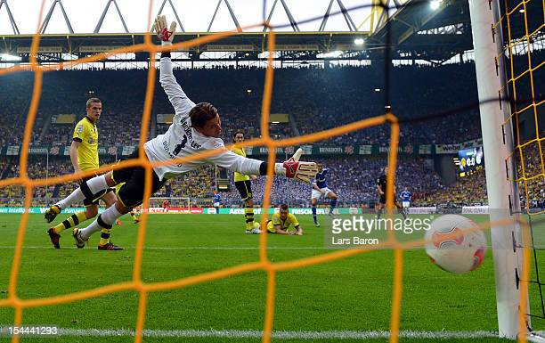 Ibrahim Affelay of Schalke scores his teams first goal against goalkeeper Roman Weidenfeller of Dortmund during the Bundesliga match between Borussia...