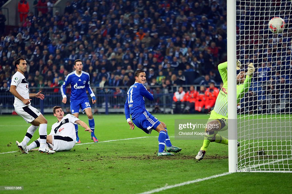 Ibrahim Affelay of Schalke (C) scores the first goal against Daniel Ischdonat of Sandhausen (R) during the DFB Cup second round match between FC Schalke 04 and SV Sandhausen at Veltins-Arena on October 30, 2012 in Gelsenkirchen, Germany.