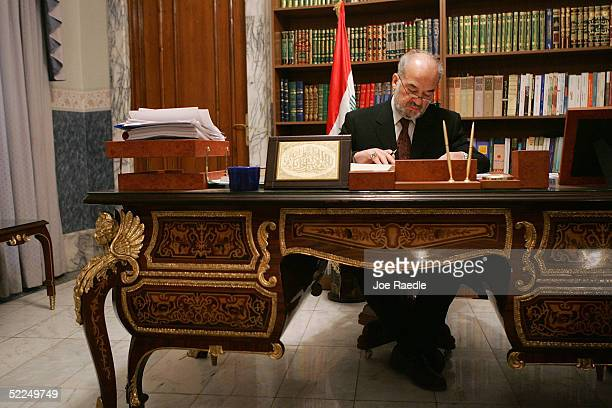 Ibrahim alJaafari frontrunning candidate for Iraqi Prime Minister reads a book taken from the shelf as he studies between meetings in his office...