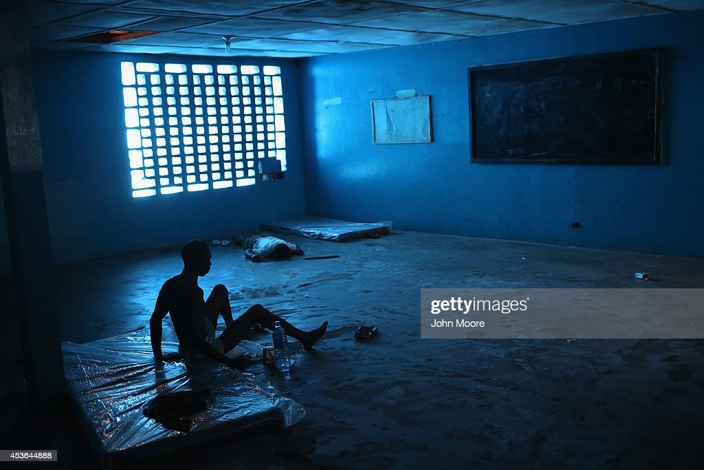 Ibrahim Fambulle sick and weak tries to stand as a corpse lies nearby in an Ebola ward on August 15 2014 in Monrovia Liberia People suspected of...