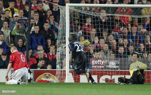 Ibrahima Bakayoko of Marseille runs away after scoring against Manchester United as a dejected Jaap Stam and Raimond van der Gouw look on at Old...