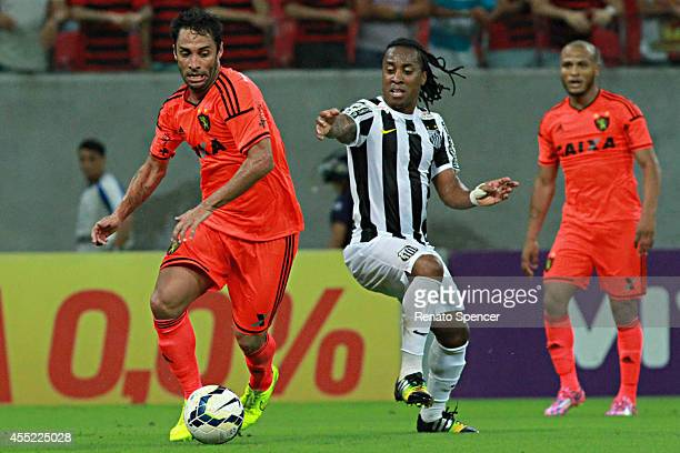 Ibson of Sport Recife battles for the ball with Arouca of Santos during the Brasileirao Series A 2014 match between Sport Recife and Santos at Arena...