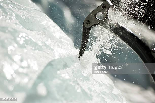 Ice axe being plunged into ice wall