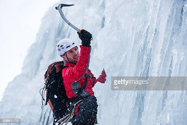- Kletterer aufsteigender einem gefrorenen Wasserfall