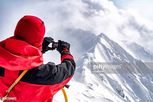 Ice climber takes a photograph atop the summit