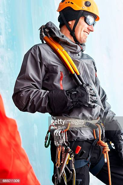 Ice climber with climbing equipment looking away smiling