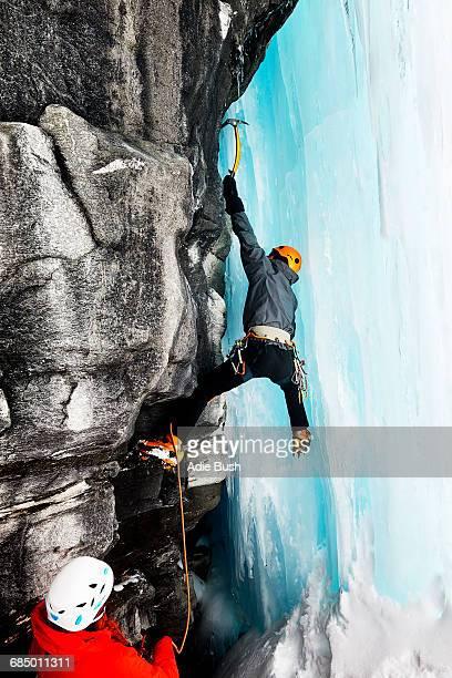 Ice climbers climbing on rock face