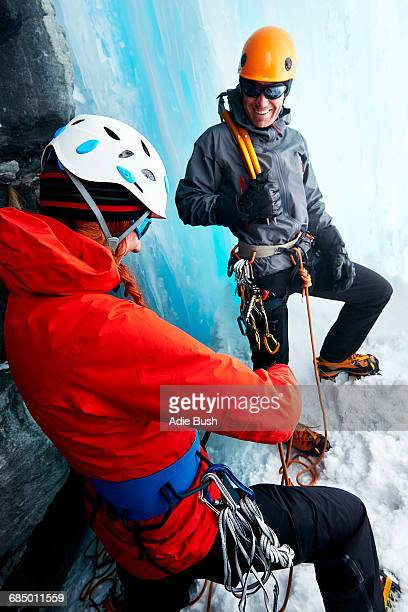 Ice climbers in ice cave preparing climbing equipment