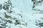 Ice climbers preparing to scale the weeping wall, frozen waterfall, Canmore, Canada