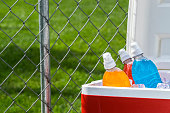 Various colors and flavors of ice cold sports drinks in a red and white ice chest with a chainlink fence behind it on a hot Summer day with shadow from a tree on the grass in the background. This coul