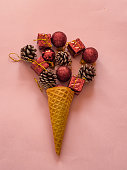 Ice cream cone with christmas decoration on pink background - summe christmas concept