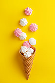 Ice cream cone with meringues on a yellow background. Sweet summer concept. Top view. Flat lay