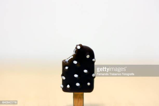 Ice cream of vanilla covered with chocolate with a small stick