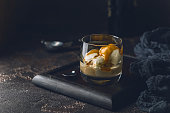 Ice cream with caramel topping and Irish cream liqueur in a glass over dark background.