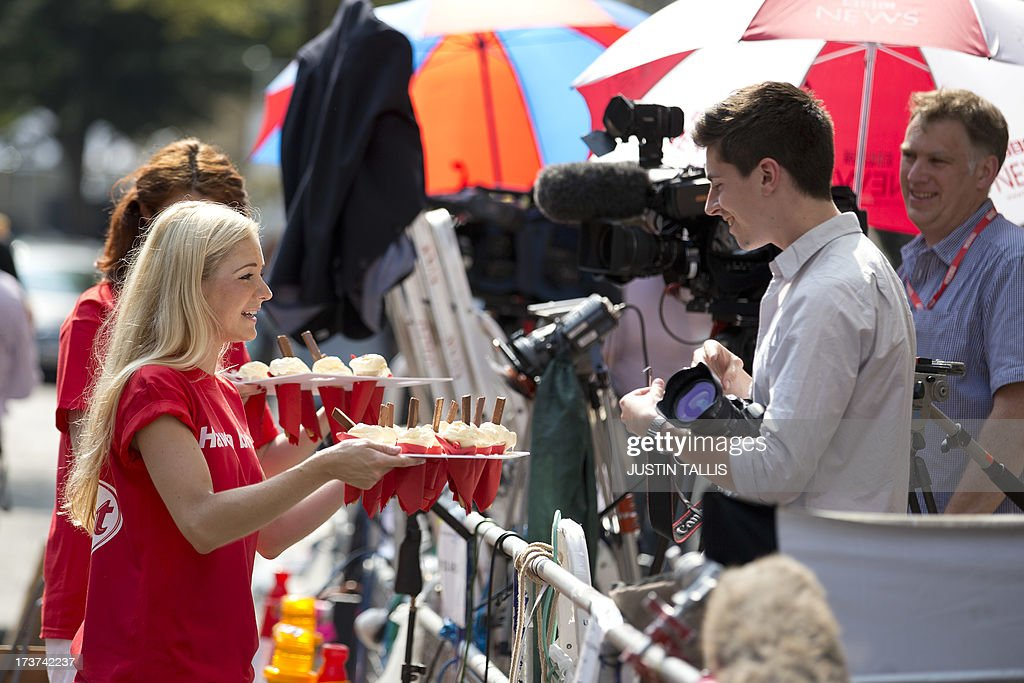 Ice creams are handed out to media representatives as part of a promotion outside the Lindo Wing of Saint Mary's Hospital in London, on July 17, 2013, where Prince William and his wife Catherine's baby will be born. Queen Elizabeth II, it seems, is just as impatient as her subjects for the royal baby to arrive this week -- because she is going on holiday.
