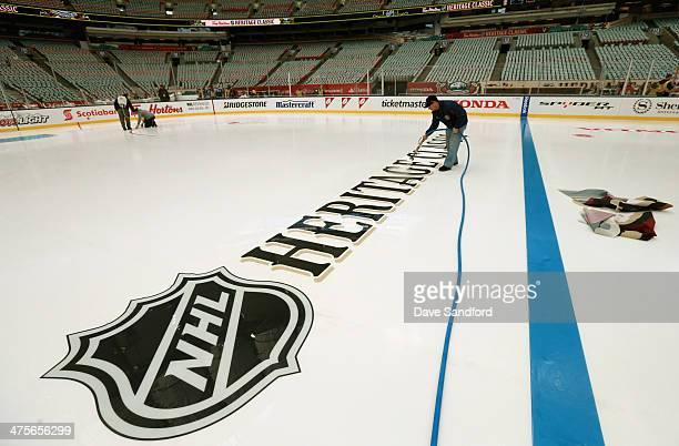 Ice crew manager Mike Craig sets the blue line logo during the 2014 Tim Horton NHL Heritage Classic build out before the game between the Vancouver...