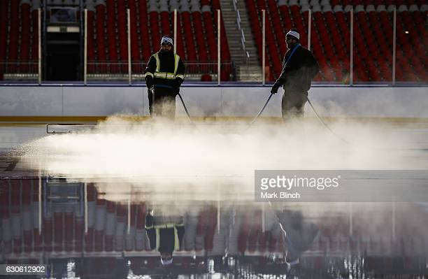 Ice crew workers spray water on the ice during the build out of the outdoor rink for the 2017 Scotiabank NHL Centennial Classic between the Detroit...