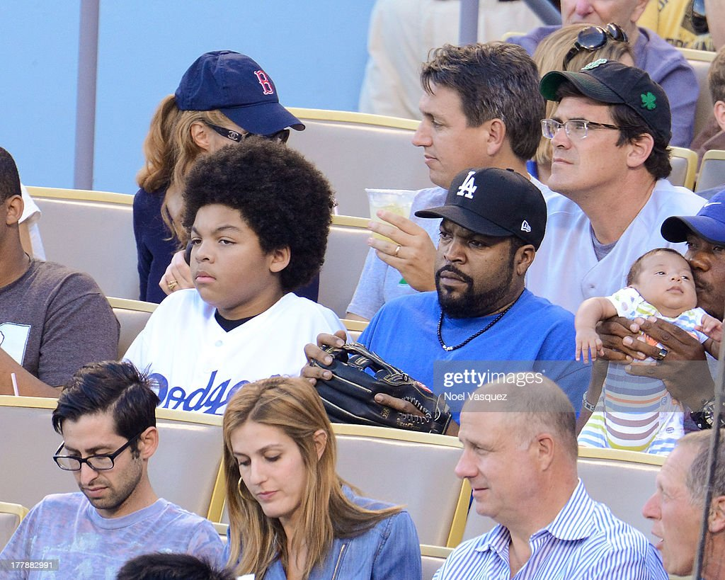 Ice Cube (R) and his son attend a baseball game between the Boston Red Sox and the Los Angeles Dodgers at Dodger Stadium on August 25, 2013 in Los Angeles, California.