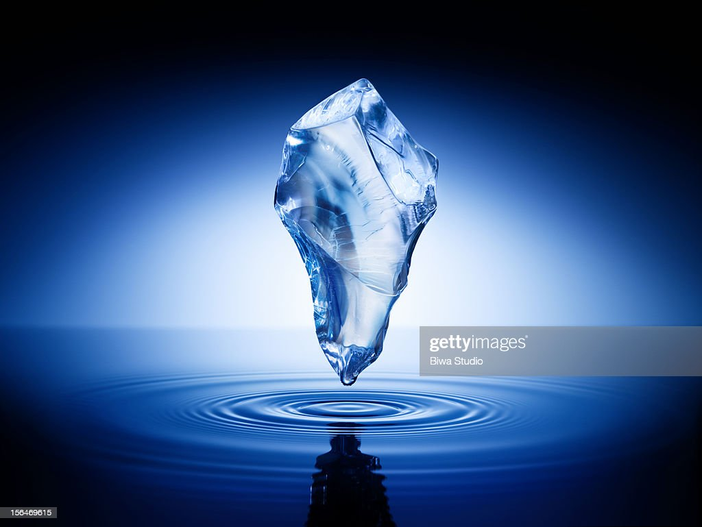 Ice cube floating in the air over water surface