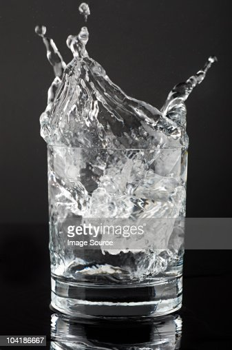 Ice cube splashing in a tumbler of gin and tonic
