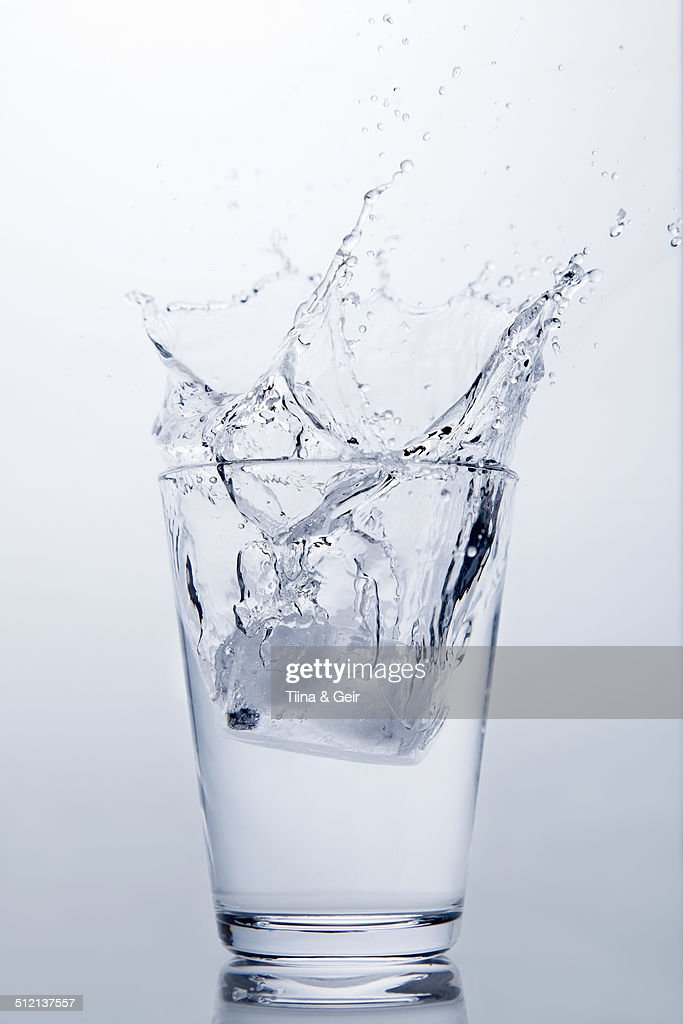 Ice cube splashing into glass of clear water