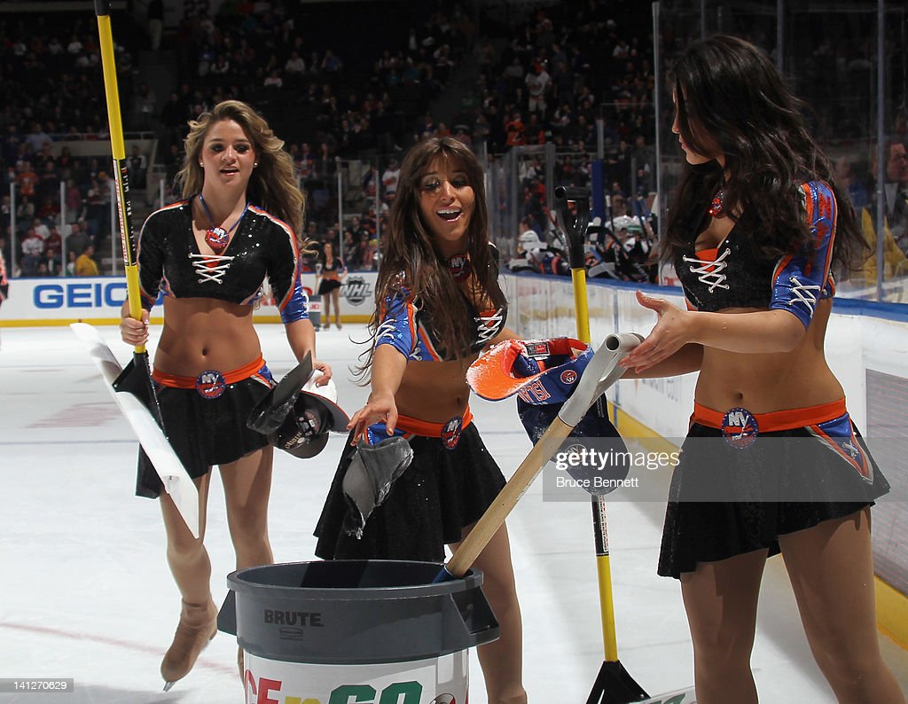 Ice girls collect hats following a goal by <a gi-track='captionPersonalityLinkClicked' href=/galleries/search?phrase=John+Tavares&family=editorial&specificpeople=601791 ng-click='$event.stopPropagation()'>John Tavares</a> #91 of the New York Islanders in the game against the Washington Capitals at the Nassau Veterans Memorial Coliseum on March 13, 2012 in Uniondale, New York. The scoring of an earlier goal by Tavares was changed thereby negating the hat trick. The Capitals defeated the Islanders 5-4 in the shootout.