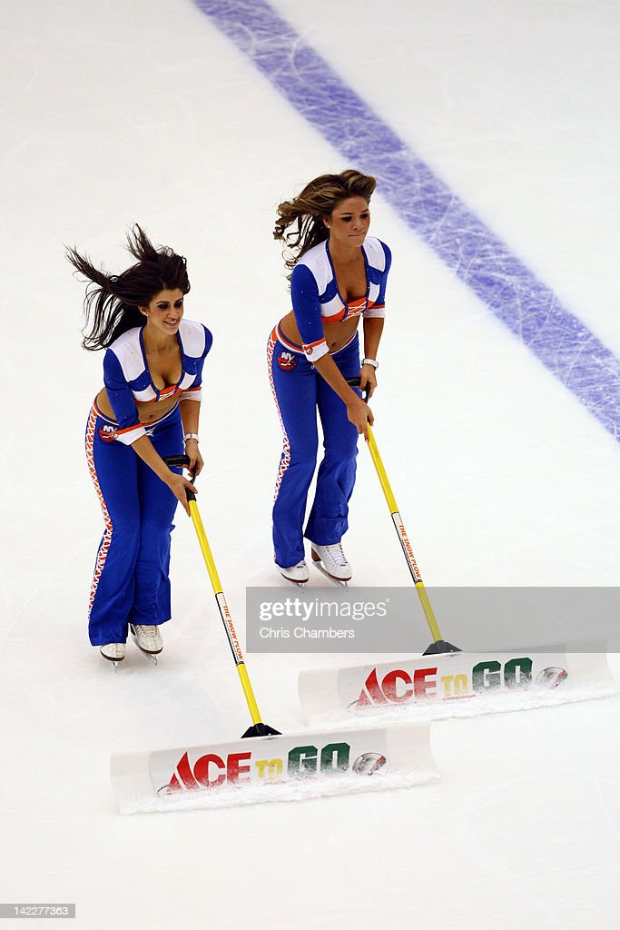 Ice girls for the New York Islanders clean the ice with shovels against the Pittsburgh Penguins at Nassau Veterans Memorial Coliseum on March 29, 2012 in Uniondale, New York.