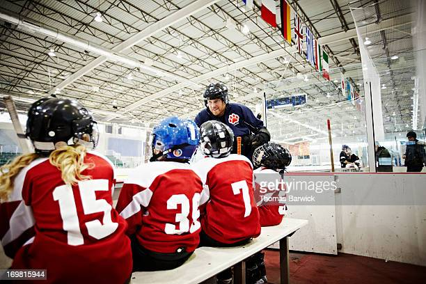 Ice hockey coach in discussion with young team