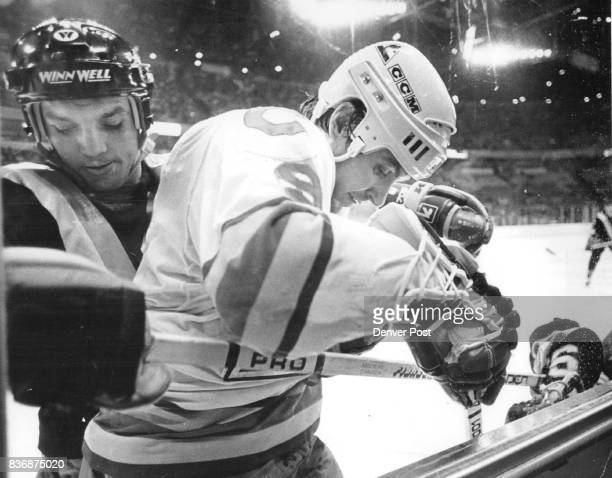 Ice Hockey Colorado Rockies Canucks' Tiger Williams dark jersey slams Denver's Don Lever against the boards as lever struggled to clear puck from...