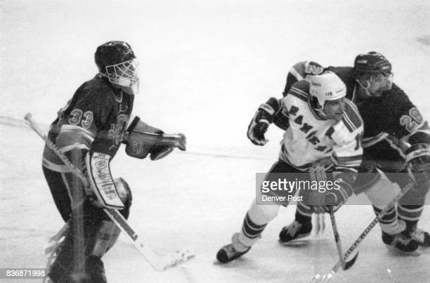 Ice Hockey Denver Rangers Denver Univer Pioria goalie Darrell May guards the net and teammate 28 Wayne Gagne holds ranger Simon Weeldon prisoner by...
