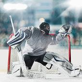 Ice hockey goal keeper catching puck