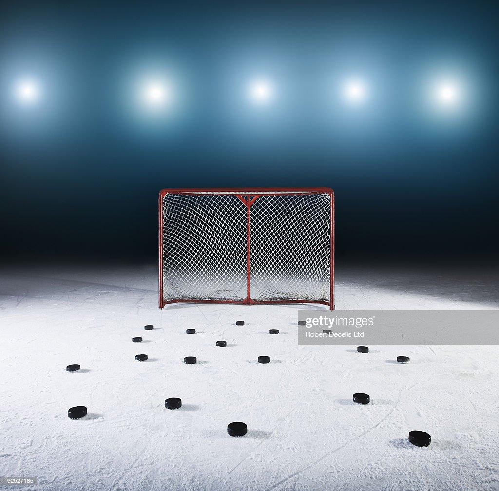 Ice hockey goal surrounded by pucks.