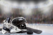 Low angle view of hockey helmet, skates; stick and puck on ice with deliberate shallow depth of field on brightly lit stadium background and copy space. Fictitious sports arena background created enti
