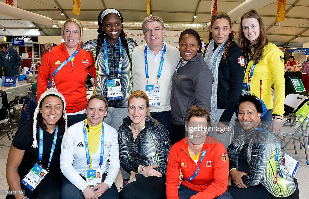 Ice hockey player Bettina Evers of Germany, bobsleigh athlete Aja Evans of the United States, International Olympic Committee (IOC) President Thomas Bach, bobsleigh athlete Lauryn Williams of the United States, bobsleigh athlete Lolo Jones of the United States, ice hockey player Ivonne Schroeder of Germany, (L-R, front) bobsleigh athlete Elana Meyers of the United States, ice hockey player Susann Goetz of Germany, bobsleigh athlete Jamie Greubel of the United States, ice hockey player Franziska Busch of Germany, and bobsleigh athlete Jazmine Fenlator of the United States pose in the athletes village prior to the start of the Sochi 2014 Winter Olympics on February 1, 2014 in Sochi. POOL/ Pascal Le Segretain