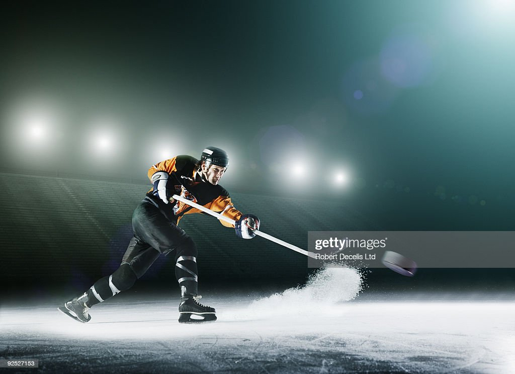 Ice hockey player passing puck.