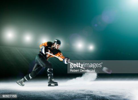 Ice hockey player passing puck.