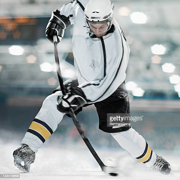 Ice hockey player shooting puck