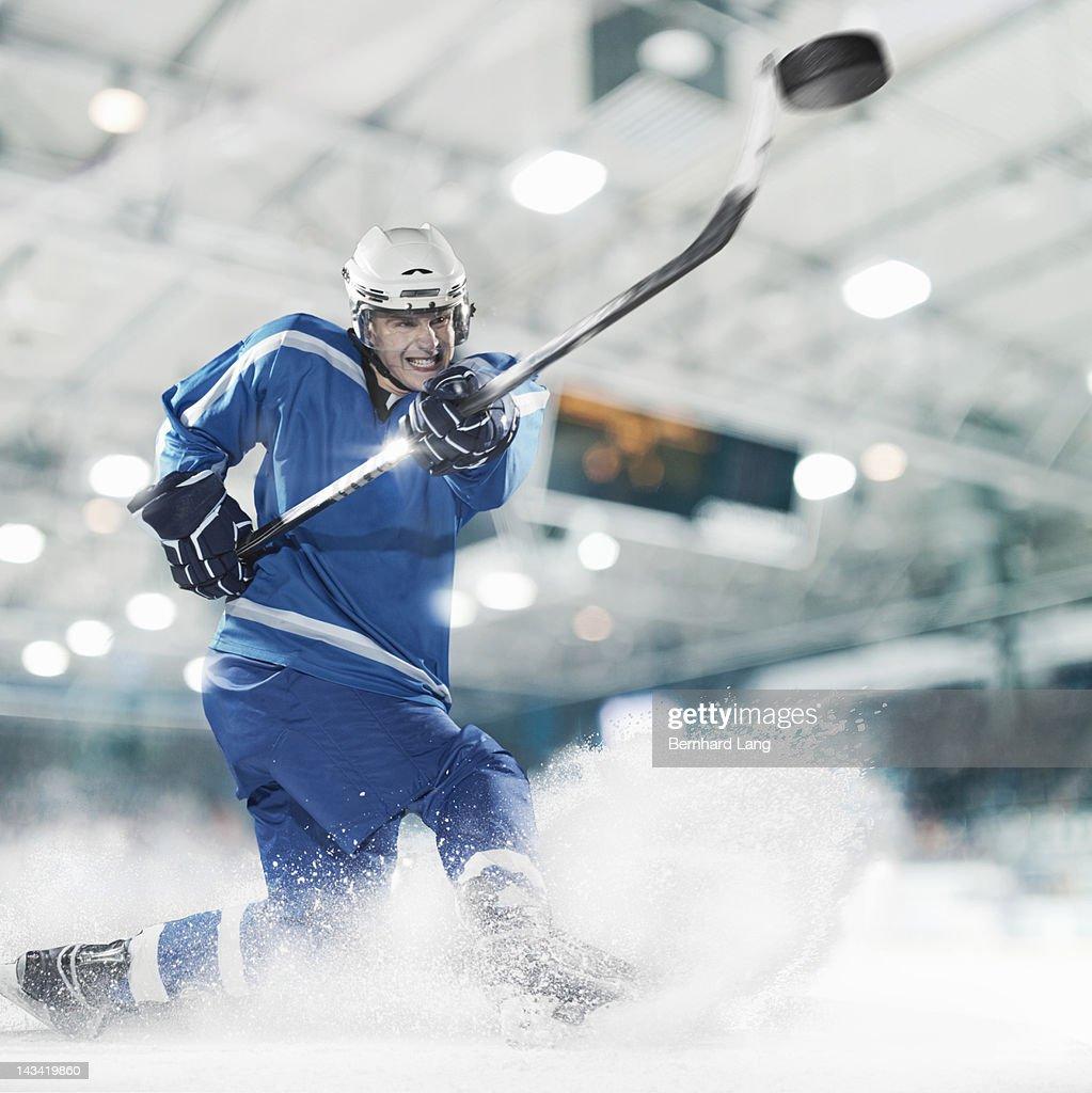 Ice hockey player shooting puck : Stock Photo