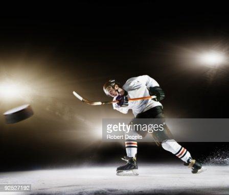 Ice hockey player shooting puck.