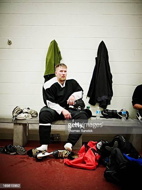 Ice hockey player sitting in locker room